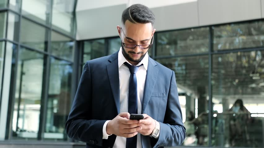 Successful Young Businessman Standing Outdoor. Working on his Mobile Phone. Settles Matters on it. Wearing Classical Clothes. Modern Hairstyle. Elegant Look. Luxurious Watch and Eyeglasses. #1014702908