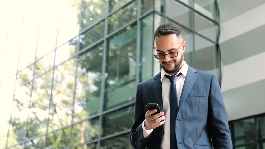 Close up view of Positive Man Standing near Office. Checking News on his Smartphone. Successful Business Project. Happily Smiling Businessman. Real Emotions. Luxury Lifestyle. Slow Motion. #1014702914