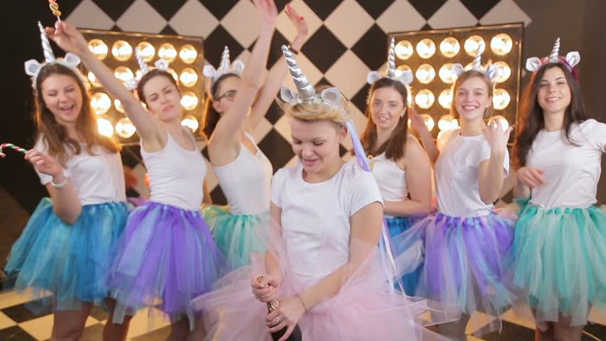 Beauty girl's in colorful air tutu skirt laughing, popping champagne on warm border light background. Joyful model having fun, celebrating hen day