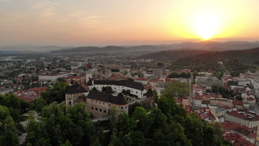 Aerial panoramic view of Ljubljana's medieval city center, capital of Slovenia, seen over Ljubljana's castle at sunset. Royalty-Free Stock Footage #1014715520