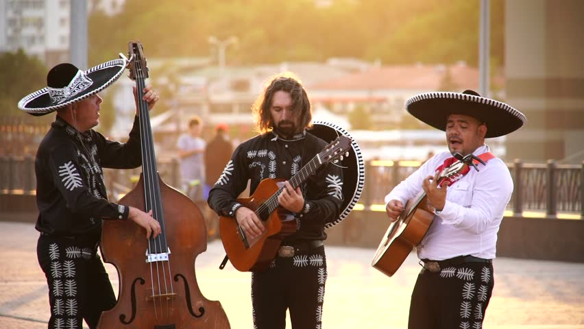 Trio of Mexican musicians mariachi give street concert in the city at sunset. Live camera