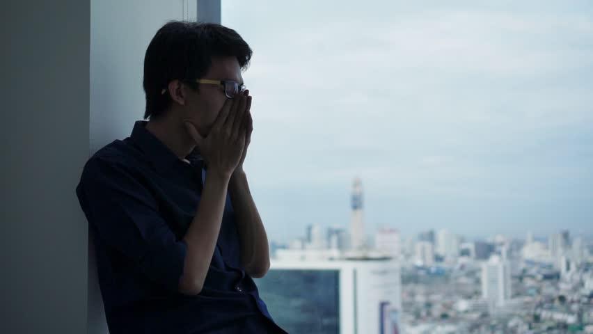 PTSD Mental health concept, Young depressed be tired  asian man massaging his nose and keeping eyes closed while sitting alone near window in evening time. #1014756662