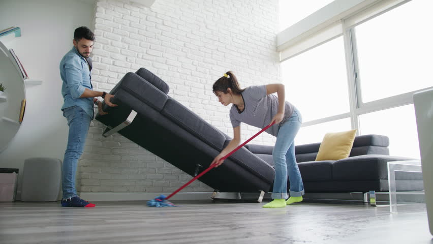 Young couple doing housework and chores. Man lifting sofa while girlfriend wipes the floor with mop. Concept of teamwork and cooperation when living together.