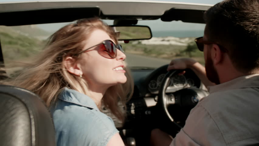 Happy couple driving in convertible to the beach, woman kisses husband while he drives on road trip