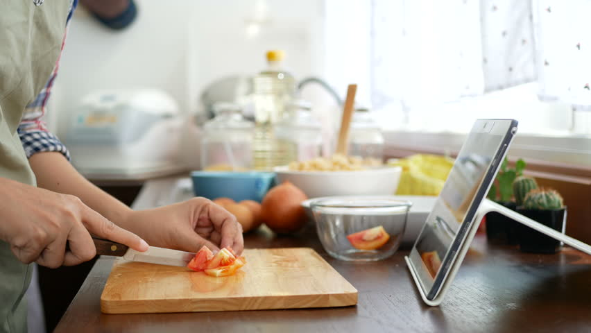 4K. woman slicing red tomato prepare ingredients for cooking follow cooking online video clip on website via tablet. cooking content on internet technology for modern lifestyle Royalty-Free Stock Footage #1014792857