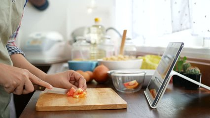 4K. woman slicing red tomato prepare ingredients for cooking follow cooking online video clip on website via tablet. cooking content on internet technology for modern lifestyle