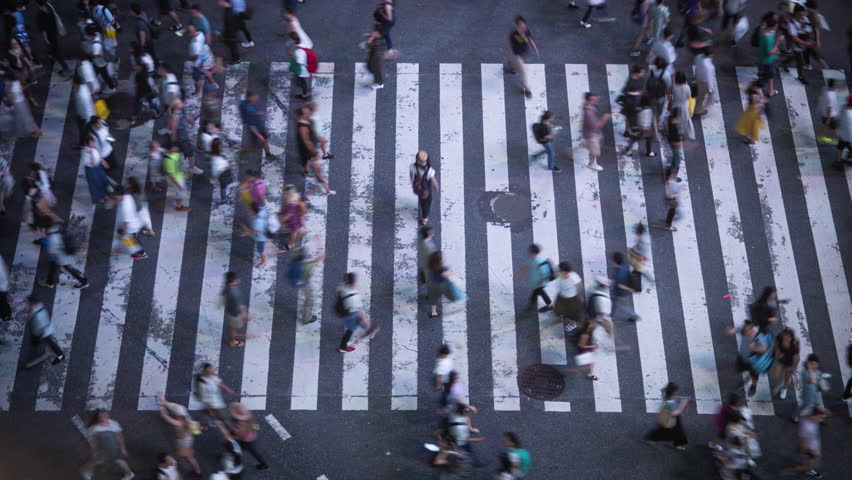 High Angle Time Lapse Shot of the Famous Shibuya Pedestrian Scramble Crosswalk with Crowds of People Crossing and Traffic. Evening in the Big City.