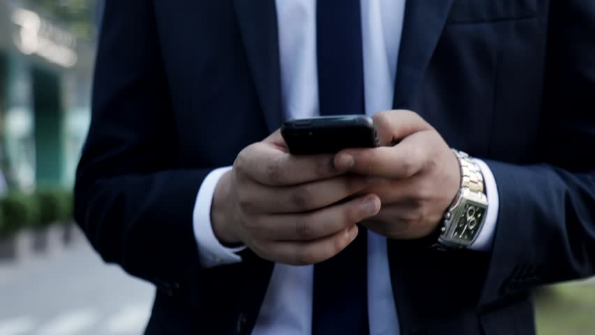 Close up of Man's Hands Holding Modern Smartphone. Businessman Walking while Typing on his Mobile Phone. Luxury Wristwatch on Man's Arm in the Foreground. Classical Black Suit.Business Lifestyle.