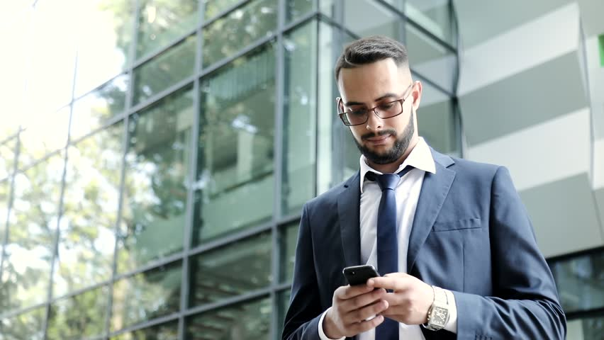 Young Attractive Bearded Man Standing by the Office Building. Sending a Message on his Phone. Looking at Smartphone's Screen. Multi ethnic People. Young Businessman Wearing Eyeglasses. | Shutterstock HD Video #1014805136
