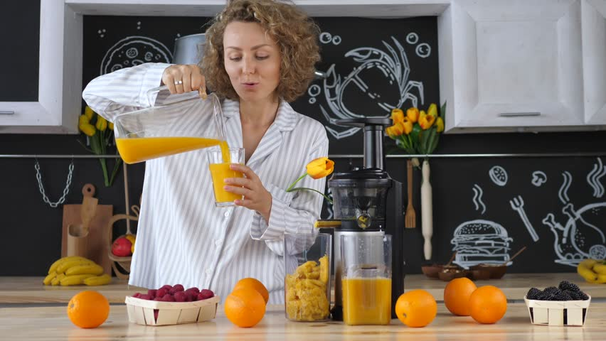 Young Woman Drinking Fresh Orange Juice In Kitchen