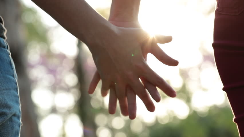 Close-up of hands joining together with sunlight flare in the background. Beautiful romantic moment between two lovers