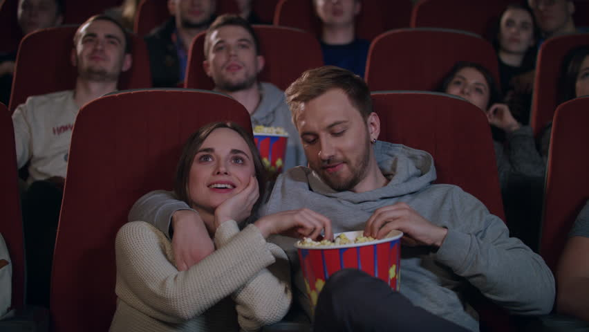 Love couple watching movie in cinema theatre. Couple in love embracing in cinema. People enjoying film and eating popcorn at cinema in slow motion. Movie entertainment