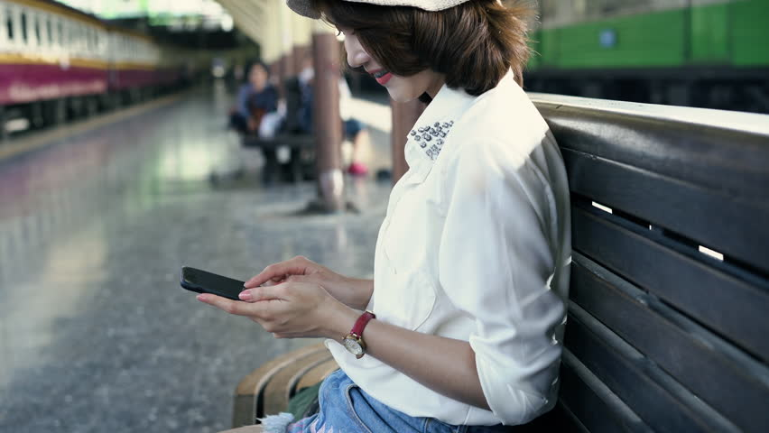 Traveler backpacker Asian woman travel in Bangkok, Thailand. Happy young female sitting on bench using smartphone for talking, reading and texting at train station. | Shutterstock HD Video #1014826720