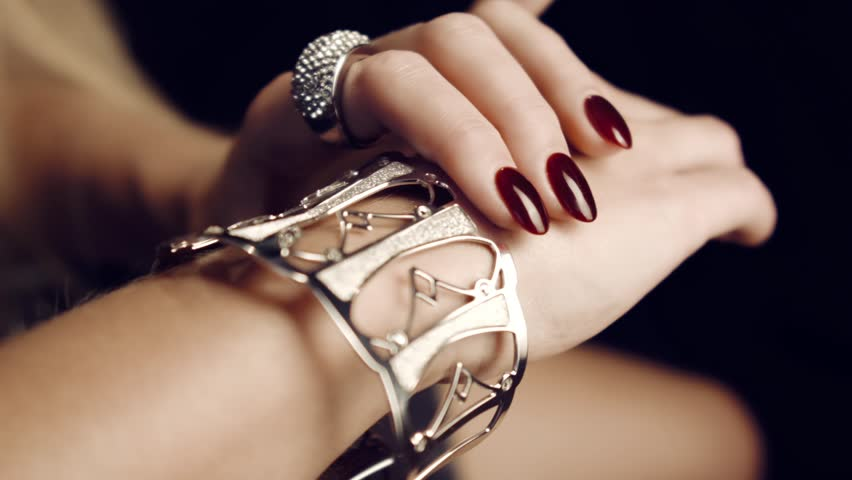 Close-up of beautiful female hands with red nails with gold big bracelet and diamond ring. Gold Jewelry for Women. Luxurious life. Advertising jewelry. In studio on black background.