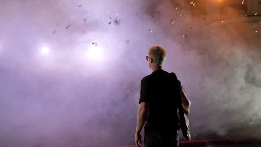 GUITARIST ON SCENE raises the guitar up, spectators applaud. The guitarist performs on stage. Stage light, smoke. From above fall golden confetti,   Shutterstock HD Video #1014861103