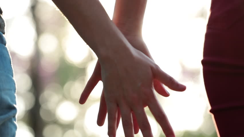 Close-up of two LGBT Lovers Joining Hands in SLOW-MOTION with sun flare #1014862861