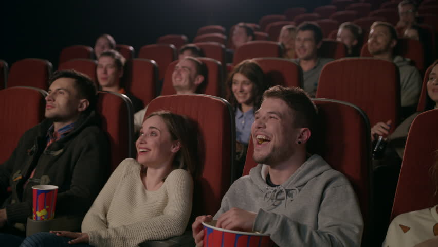 Young people laugh at comedy movie in cinema theatre. Young people laughing at cinema watching amusing comedy. Cheerful people watching comedy film in slow motion #1014864658