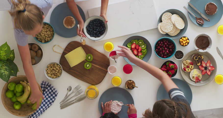 above view group of young creative multi ethnic girls making tasty homemade sweets together healthy vibrant food in kitchen time lapse rotate #1014902368