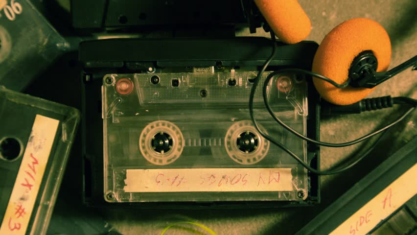 Spinning cassette tape in a walkman and a few old cassettes | Shutterstock HD Video #1014903883