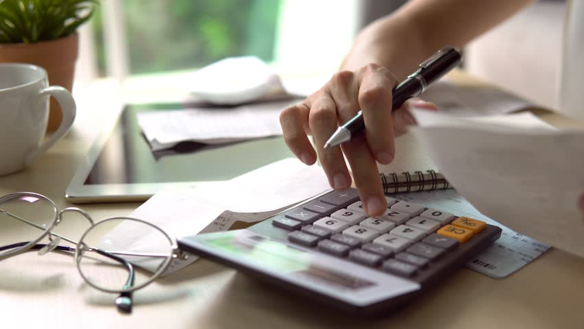Stressed young woman checking bills, taxes, bank account balance and calculating expenses in the living room at home | Shutterstock HD Video #1014911920