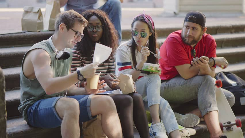 Multicultural group of friends eating and discussing their study during lunch break. Students having meal and rest between lessons sitting on canteen stairs.