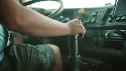 Dump Truck Driver At The Wheel and shift gear