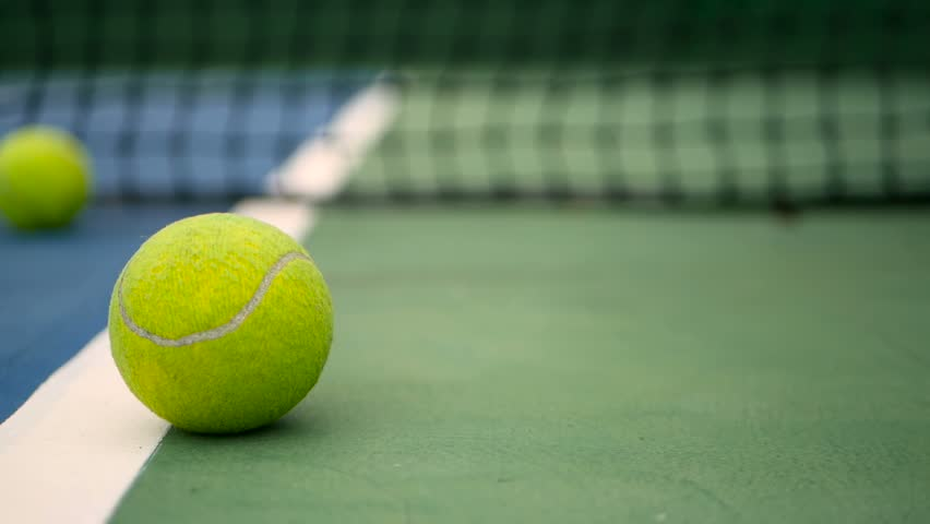 Close up of tennis equipment on the court. Sport, recreation concept. Yellow tennis balls in motion on a clay green blue court next to the white line with copy space, soft focus and net in background. #1014932521