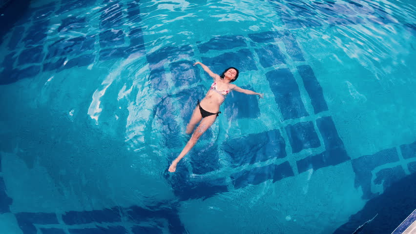 Aerial view of lying on water surface in big swimming pool   Shutterstock HD Video #1014940414