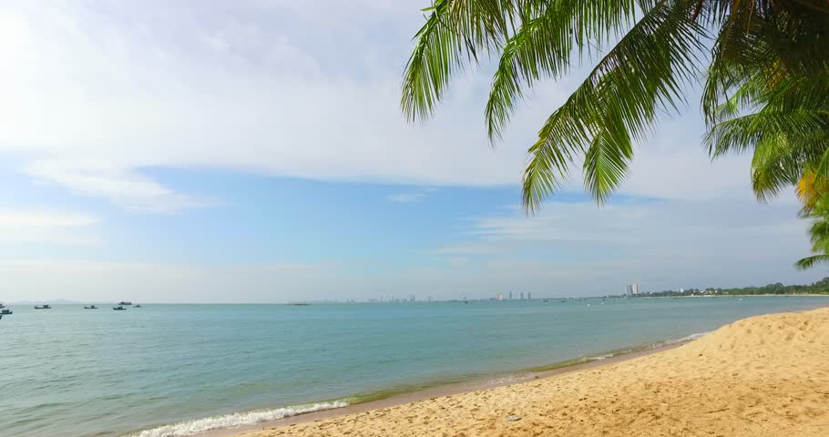 Coconut palm trees on the beach in Thailand. Beautiful beach, Bang Saray beach in CHONBURI, THAILAND. Coconut trees with blue sky for beautiful beach concept. Free space for text. Handheld movement 4K   Shutterstock HD Video #1014945568