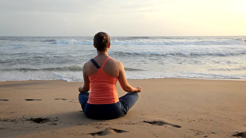 Woman doing yoga - meditate and relax in Padmasana Lotus asana pose with chin mudra outdoors at tropical beach on sunset   Shutterstock HD Video #1014949474