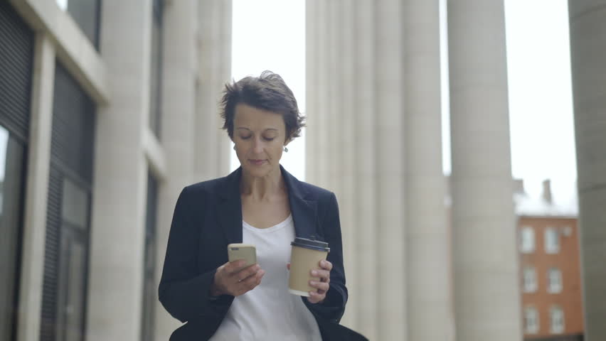 Medium dolly shot of elegant middle aged businesswoman with short hair walking down street with cell phone and takeaway coffee cup in her hands and looking around thoughtfully