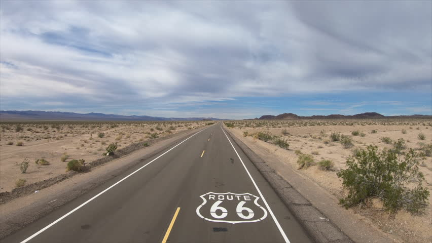 Aerial fly over of historic Route 66 pavement sign in the scenic California Mojave desert.
