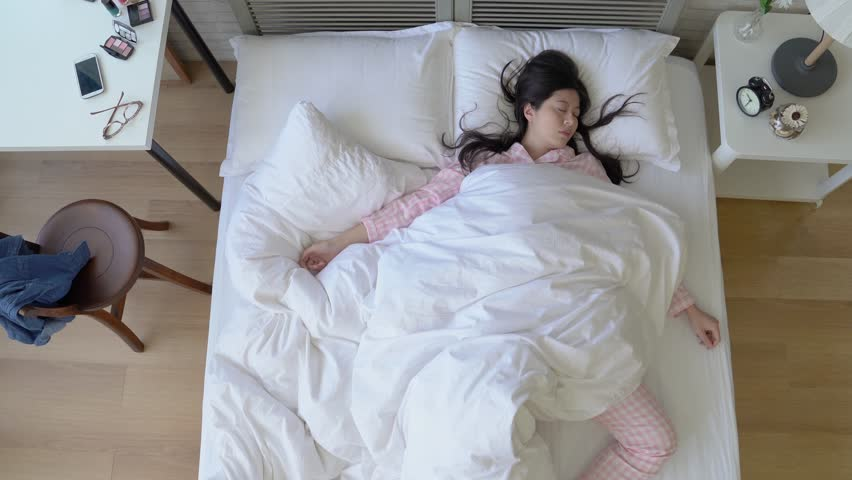 Asian exhausted woman lying in the bed and sleep deeply. She sleeps in different positions and postures.   Shutterstock HD Video #1014964564