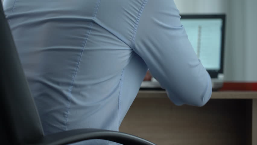 Male office worker feeling sharp back pain, standing up, sedentary lifestyle