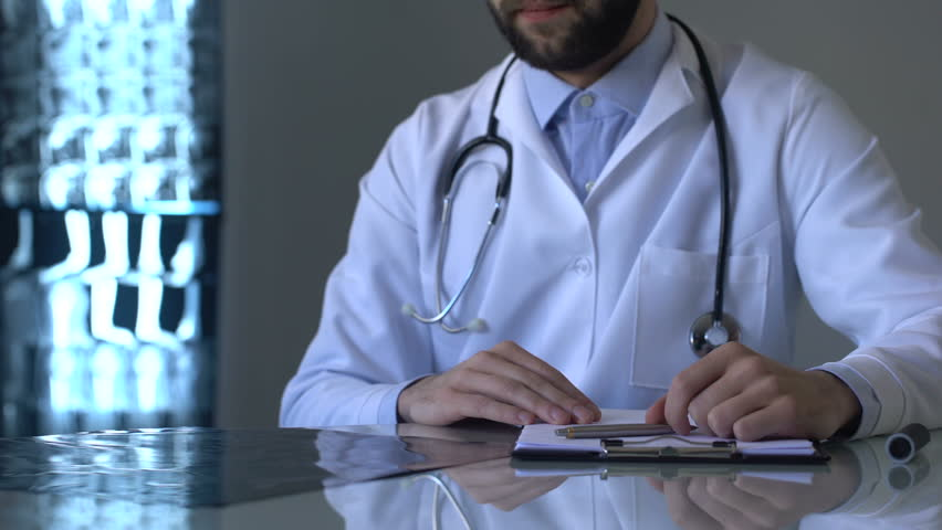 Oncologist examining brain x-ray and writing diagnosis in medical form, health | Shutterstock HD Video #1014981838