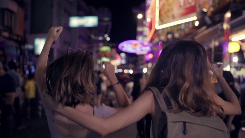 Slow motion - Traveler backpacker Asian women lesbian lgbt couple dancing together. Female drinking alcohol or beer with friends and having party at The Khao San Road in Bangkok, Thailand.