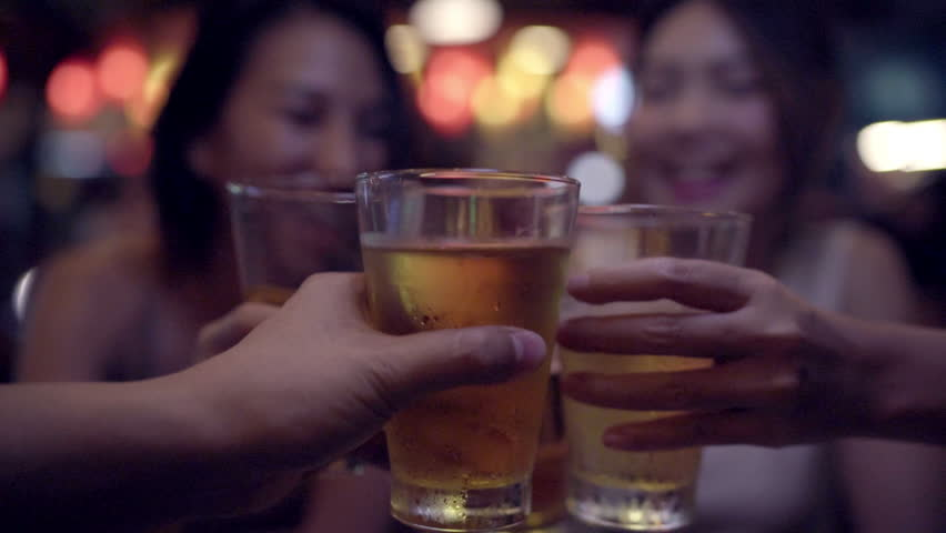 Slow motion - Traveler backpacker Asian women lesbian lgbt couple travel in Bangkok, Thailand. Female drinking alcohol or beer with friends and having party at The Khao San Road. | Shutterstock HD Video #1015004479