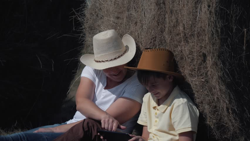 Happy family mother and son with a tablet sitting in the field, leaning on a hay-roll. The concept of a happy family