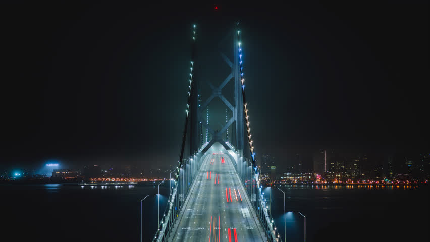 Bay Bridge at night with the illuminated light from cars. Time-lapse with straight view of the famous landmark of San Francisco city, California, North America, USA.