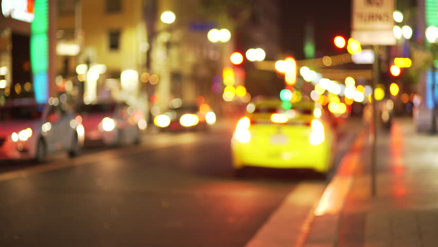 Blurry background plate of taxi cab line parked on city street downtown at night. Out of focus Video backdrop of urban area with bokeh lights for green screen compositing. 4k