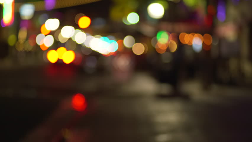 Background plate of out of focus city street sidewalk at night with bokeh headlights passing by and pedestrians. Blurry Video backdrop for green screen compositing. 4k