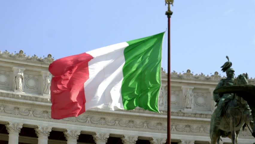 Italian flag waving against the equestrian statue representing the Italian King Vittorio Emanuele II. Altar of the Fatherland from Piazza Venezia, Rome, Italy