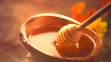 Honey dripping, pouring from honey dipper in wooden bowl.  Close-up. Healthy organic Thick honey dipping from the wooden honey spoon, closeup. 4K UHD video footage. Slow motion