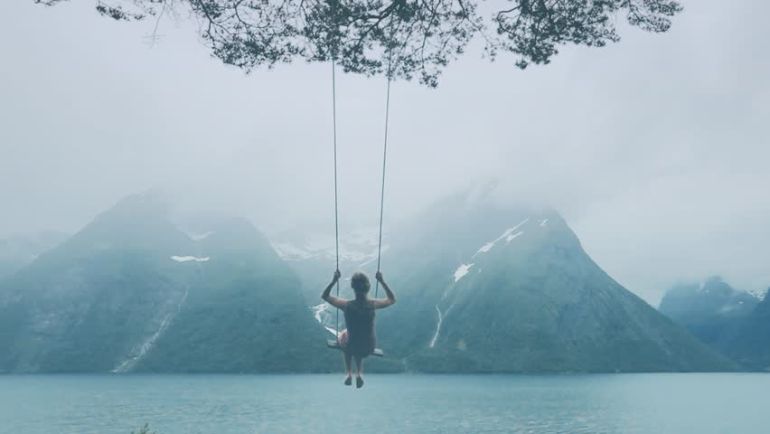 Dream concept, beautiful young woman on the swing in fjord Norway, inspiring landscape | Shutterstock HD Video #1015037857