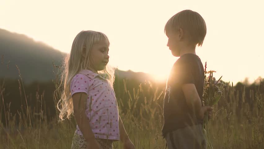 Little boy gives the girl a bouquet of flowers in the field at sunset
