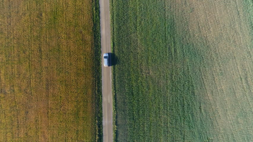 Aerial top down view of car driving on country road. Drone shot flying over fields, tree and gravel road Royalty-Free Stock Footage #1015051633