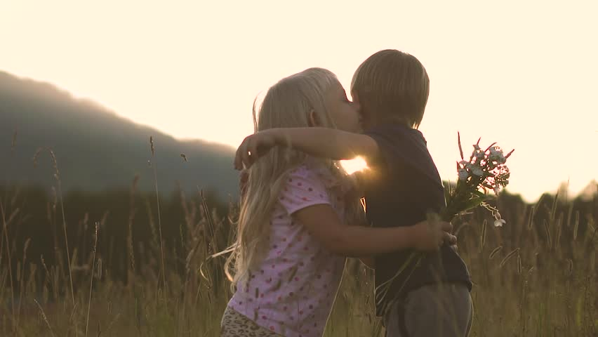 Little girl in the field at sunset, kisses the boy for what he gave her flowers