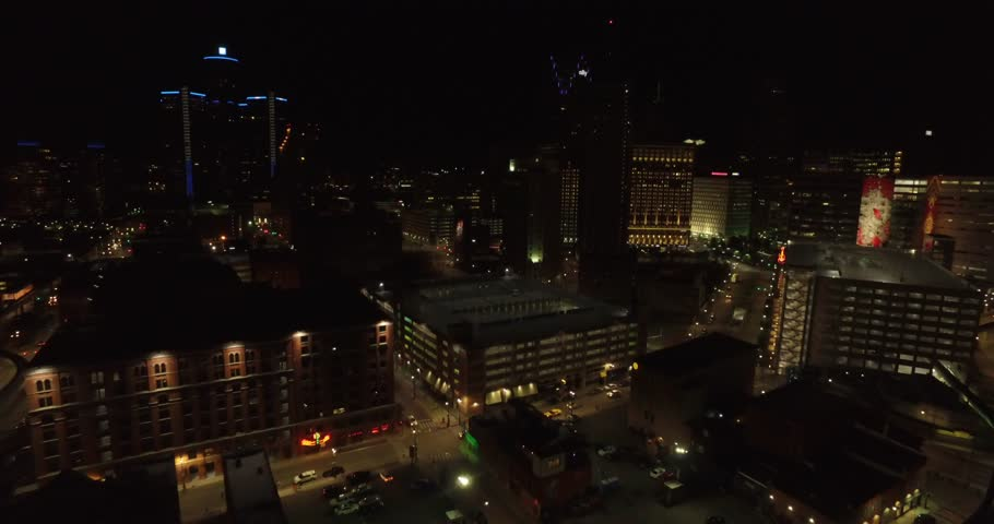 Aerial at night of Detroit Michigan downtown. You can see office buildings and cars driving on the street as the street lights glow in the night.