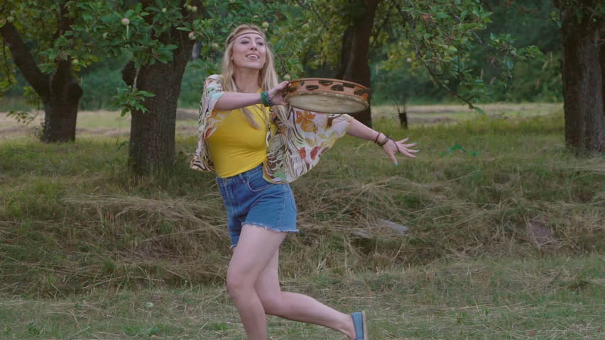 young blond hippie woman dancing with a tambourine on the grass in the park at sunset. Warm summer day and soft backlight. happy woman is dancing. the middle plan. a hot summer day.