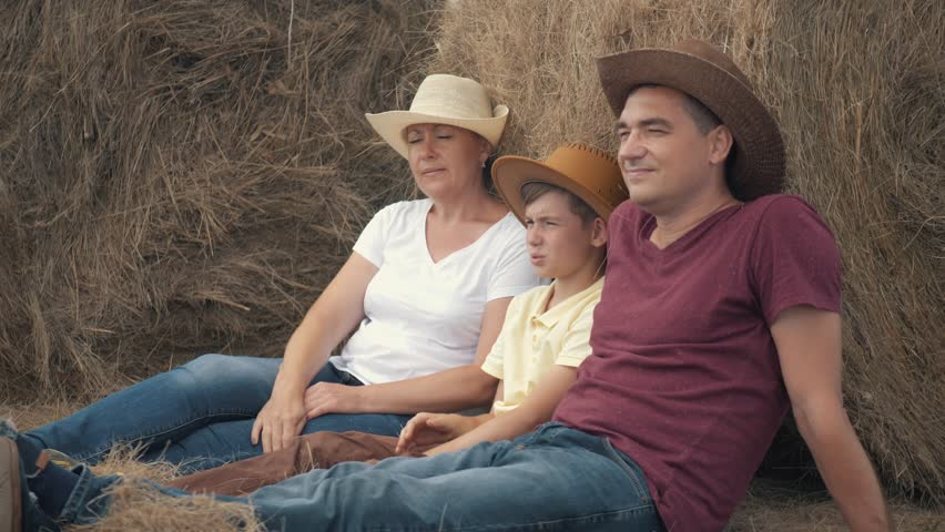 Happy family mother, father, and son with a tablet sitting in the field, leaning on a hay-roll. The concept of a happy family